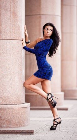 very beautiful young brunete woman wearing a blue mini dress in the street photo