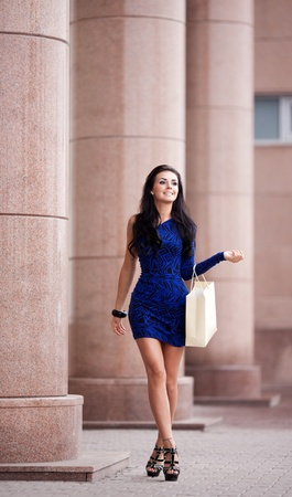 very beautiful young brunete woman with a paper bag going shopping in the sity photo