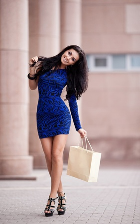 very beautiful young brunette woman with a paper bag going shopping in the city photo