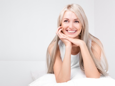 beautiful young blond woman on the bed at home photo
