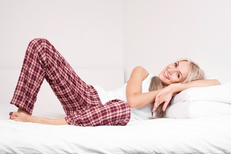 sleepwear: beautiful young blond woman on the bed at home Stock Photo