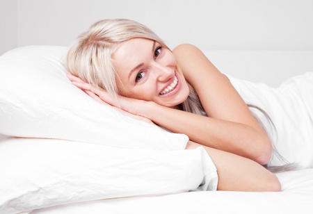 beautiful young blond woman on the bed at home Stock Photo