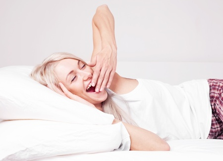 beautiful young blond woman waking up, yawning and stretching on the bed at home photo