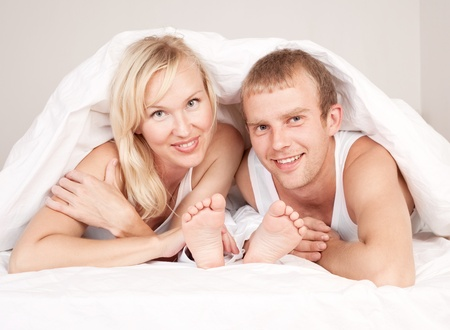 happy family; mother ,father and their son under the balnket in  bed at home   photo