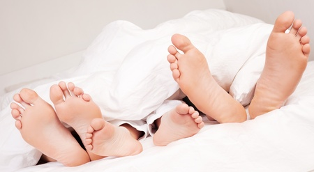 happy family; feet of a mother ,father and their son under the balnket in  bed at home Stock Photo - 10088314