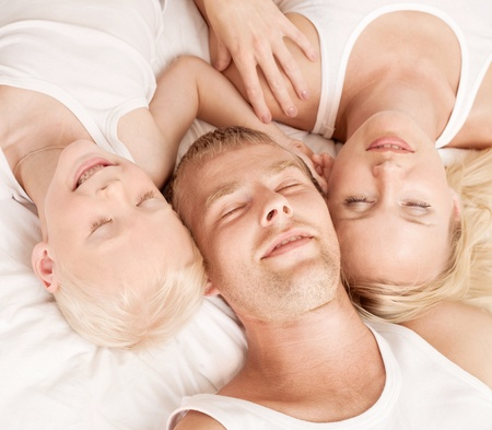 happy family; mother ,father and their son sleeping in  bed at home  photo