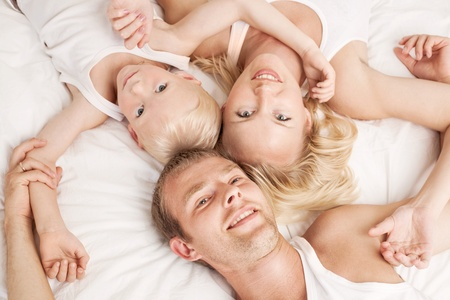 happy family; mother ,father and their son in  bed at home  photo