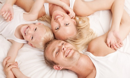 happy family; mother ,father and their son in  bed at home Stock Photo - 10088516