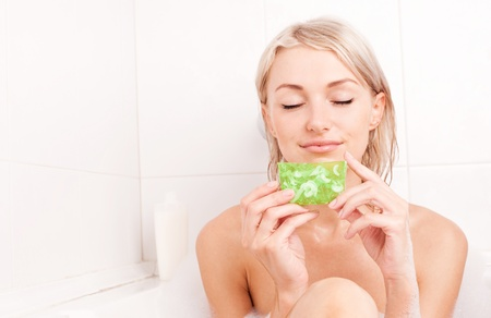 glycerin soap: beautiful young blond woman taking a bath and using a homemade glycerin soap Stock Photo