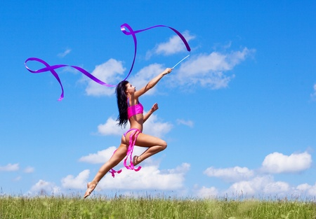 happy jumping young woman with a ribbon outdoor on a summer day photo