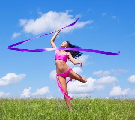 optimismo: feliz bailando a joven con una cinta al aire libre en un día de verano