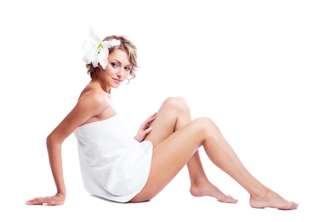 beautiful young blond woman wrapped into the towel  with a lily in her hair, isolated against white background photo