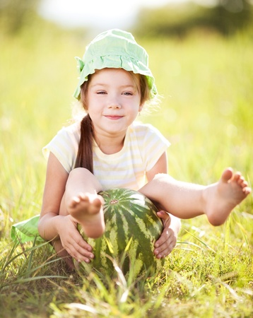 forest products: cute little girl with watermelon on the grass in summertime Stock Photo