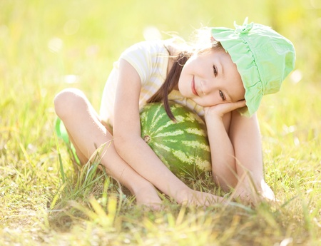 outsides: cute little girl with watermelon on the grass in summertime Stock Photo