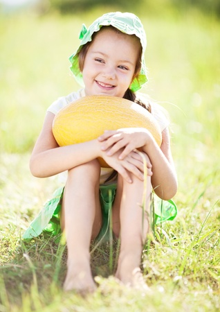 melon field: cute happy  little girl with melon on the grass in summertime