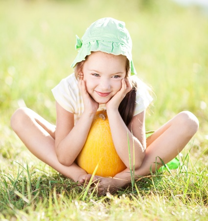 outsides: cute happy  little girl with melon on the grass in summertime