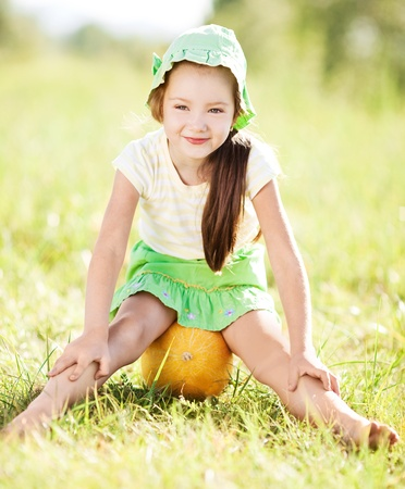 forest products: cute happy  little girl with melon on the grass in summertime