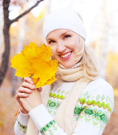 outsides: beautiful young blond woman spending time in the park and holding maple leaves