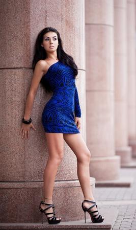 piernas con tacones: joven Brunete muy hermosa que desgasta un mini vestido azul en la calle