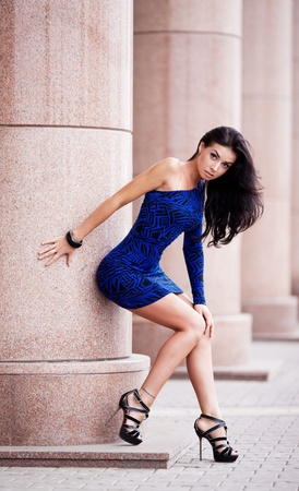 high street: very beautiful young brunete woman wearing a blue mini dress in the street
