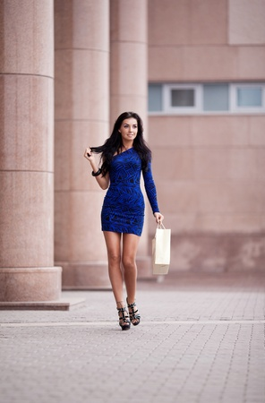 high street: very beautiful young brunette woman with a paper bag going shopping in the city