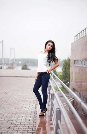 beautiful lonely young brunette woman wearing jeans and high heels in the street photo