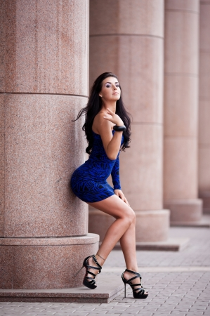 very beautiful young brunette woman wearing a blue mini dress in the street photo