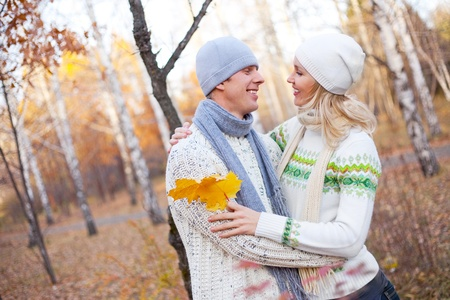 woman sweater: happy young couple spending time outdoor in the auatumn park