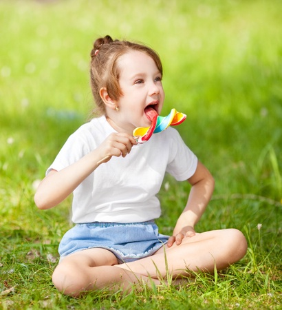 girl licking: cute little girl eating a lollipop on the grass in summertime Stock Photo