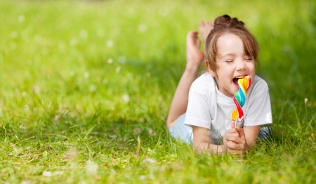 cute little girl eating a lollipop on the grass in summertime Stock Photo