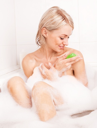 beautiful young blond woman taking a bath with foam and using a homemade glycerin soap photo