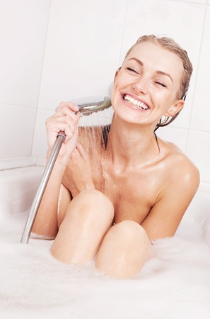 taking shower: beautiful young blond woman taking a relaxing bath with foam and using a shower Stock Photo