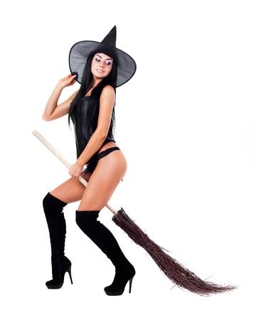 довольно молодая брюнетка сексуальная ведьма с метлой, изолированных на белом фоне