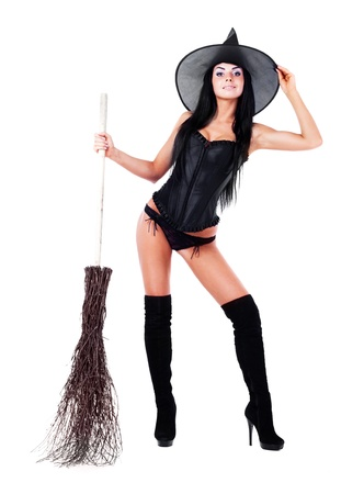 pretty sexy young brunette witch with a broom, isolated against white background