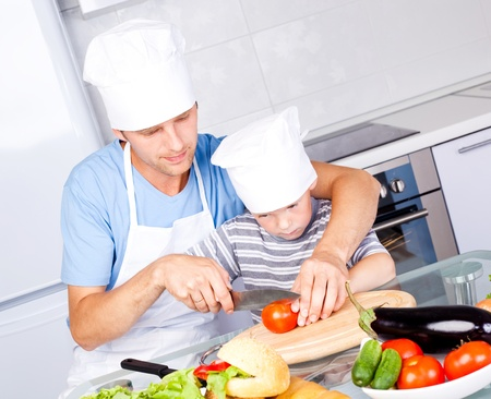 young father and his five year old son cook together in the kitchen at home