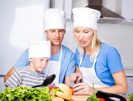 young family; father, mother and their five year old son cook together in the kitchen at home photo