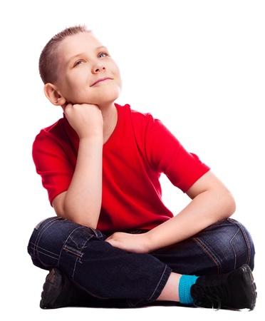 bambini pensierosi: sognante ragazzo dieci anni seduta sul pavimento, isolato contro bianco
