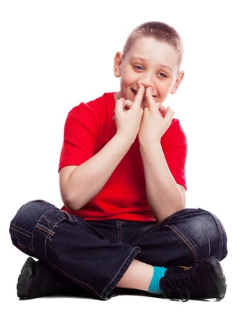 ten year old boy picking his nose , isolated against white background photo