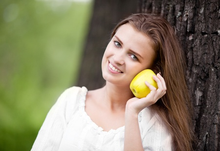 outsides: beautiful happy young woman with an apple in the park  on a warm summer day