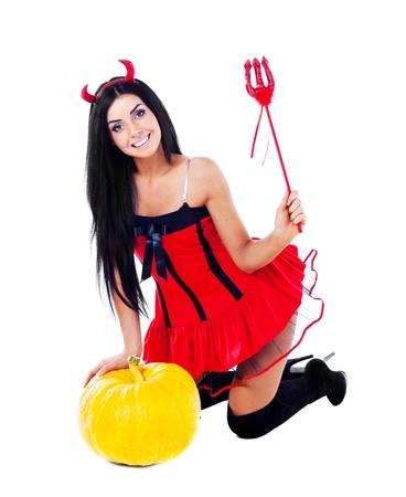 sexy junge Brünette Frau als Teufelchen verkleidet mit einem Kürbis Standard-Bild