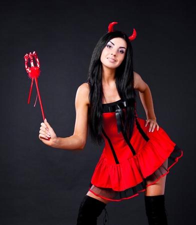 evil girl: sexy ragazza bruna indossa un costume di Halloween di un folletto, isolato su sfondo nero Archivio Fotografico