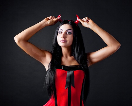 imp: sexy brunette girl wearing a halloween costume of an imp, isolated against black background Stock Photo