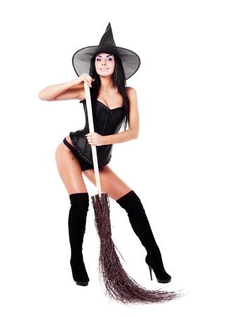 tacones negros: bastante sexy joven bruja morena con una escoba, aislada sobre fondo blanco