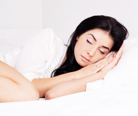 sexy young brunette woman wearing a white shirt sleeping on the bed at home Stock Photo - 10517129