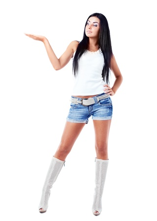 here: sexy young brunette woman with her hand up, place your product here, isolated against white background Stock Photo