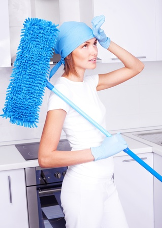 beautiful tired young housewife with a mop in the kitchen Stock Photo - 10524229