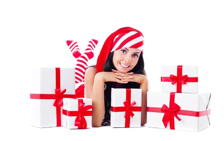 santa helper: beautiful young brunette woman dressed as Santa sitting on the floor with a lot of presents