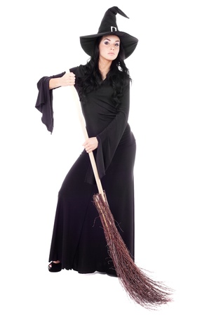 sexy halloween girl: pretty sexy young brunette witch with a broom, isolated against white background