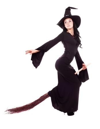 bruja: bastante sexy joven bruja Morena volando en una escoba, aislada sobre fondo blanco Foto de archivo
