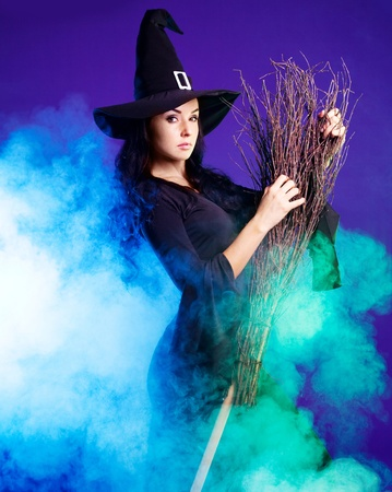 angry sexy young brunette witch with a broom and foam around her, isolated against white background photo